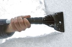 Scraping snow and ice from the car windscreen Royalty Free Stock Images