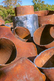 Scraps of big metal rusty pipes outdoors. Scraps of big metal rusty curved pipes Royalty Free Stock Photos
