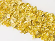 Scraps of gold foil in diagonal Royalty Free Stock Photos