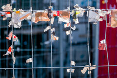 Scraps of paper against a wire fence Royalty Free Stock Photo