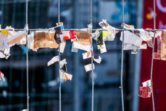 Scraps of paper against a wire fence Royalty Free Stock Images