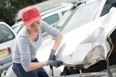 Scrapyard pracownik z wypadek uszkadzającym samochodem fotografia stock