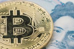 Scratch bear market Bitcoin cryptocurrency, digital money in Jap. An concept, closed up shot of physical coin with B sign alphabet on face of Japanese  banknotes Stock Photo