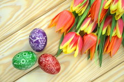 Scratched handmade Easter eggs and tulips Stock Image