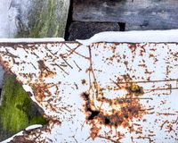 Scratched metal sheet and rusty holes background. Wooden board covered with green moss stock photography