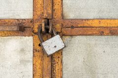 The scratched old padlock closes gray metal door or gate, abstract background. Scratched old padlock closes gray metal door or gate, abstract background royalty free stock image