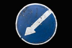 Scratched round blue road sign `Keep Left` isolated on black.  Royalty Free Stock Photo