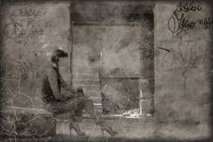 Scratched sepia toned photo women sitting on tire in slum Stock Image