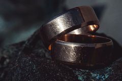Scratched two wide gold wedding rings on stone surface Stock Photography
