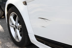 Scratched vehicle. White vehicle on a road side with black scratch mark on left door Stock Photo