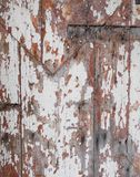 Scratched wood door detail. Vertical close up of scratched painted wood door detail royalty free stock photo