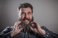 Scratching huge beard portrait, mature adult Caucasian man. Scracthing face with both hands, Huge beard portrait, mature adult Caucasian man Royalty Free Stock Photo