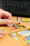 Scratching lottery tickets with computer background. Royalty Free Stock Images