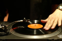 Scratching the record. A DJ's hand scratches Stock Images