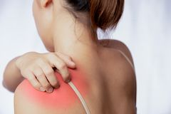 Scratching on skin at left shoulder. Young woman scratching on skin of left shoulder area, rash at left side of Asian woman stock photo