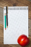 Scratchpad for taking notes, a pen, a pencil and an apple Stock Image