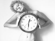 Scrawny blond girl with big clock in hands Royalty Free Stock Image
