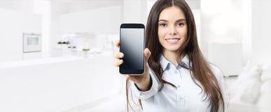 Scre de sorriso esperto do telefone celular da exibição da mulher do conceito de controle da casa fotos de stock royalty free