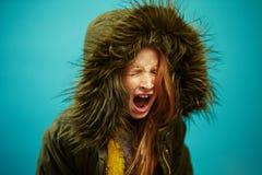 Scream девушка детей в куртке зимы на предпосылке изолированной синью стоковое изображение