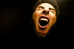 Scream. Face of a screaming man with mouth open wide on black background Stock Photos
