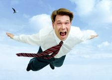 Scream. Conceptual image of young businessman shouting while flying in the clouds Stock Photography