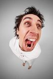 Scream. Fish eye shot of screaming insane man in strait-jacket on grey background Stock Photos