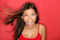 Scream. Woman ing wild and crazy at full energy looking at camera on red background. Beautiful mixed race Asian Caucasian brunette female model with wind in Royalty Free Stock Image