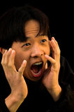 Scream. A young Asian man with a shocked expression on his face royalty free stock photo