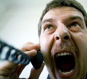 Scream of angry stressed man at phone Royalty Free Stock Photos