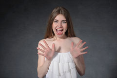 Scream, disgust, revulsion concept. Woman is closed from danger. Against a dark gray background Royalty Free Stock Images