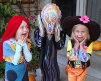 Scream on Halloween. Two girls in costumes scream for their lives as they are confronted by a life-sized version of the character on Halloween stock photo