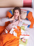 Scream in pain. Young woman is ill in bed. She is feeling miserable. She is screaming in pain. Ideal medical shot Stock Images