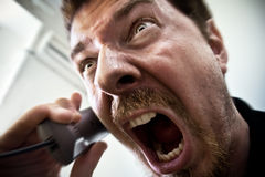 Scream of stressed man at phone. Extreme angry man shouting at the phone Royalty Free Stock Photography