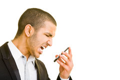Screaming. Young business man screaming into his mobile phone Royalty Free Stock Photography