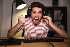 Screaming angry gamer playing video games on computer. While sitting by the table at home royalty free stock photos