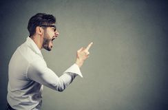 Screaming angry man with accusation. Side view of man threatening with finger while shouting loudly and looking away Stock Photography