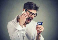 Screaming angry man solving problems with credit card. Angry young man talking on the phone while holding credit card and arguing expressively Stock Photo