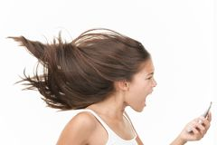 Screaming angry mobile phone woman. Screaming angry woman on the mobile phone. Dynamic and energetic image of young mixed race chinese / caucasian woman isolated Royalty Free Stock Photo