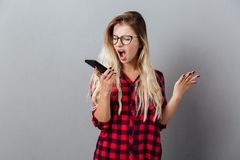 Screaming angry young blonde woman talking by phone. Picture of screaming angry young blonde woman wearing glasses standing isolated over grey wall. Looking Royalty Free Stock Images