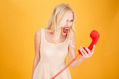 Screaming angry young blonde woman talking by telephone. Photo of screaming angry young blonde woman standing isolated over yellow wall background. Looking Royalty Free Stock Photo