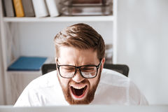 Screaming angry young businessman looking at computer. Photo of screaming angry young businessman wearing glasses dressed in white shirt sitting in office and Royalty Free Stock Photos