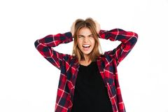Screaming angry young woman looking camera. Photo of screaming angry young woman standing isolated over white wall background. Looking camera Royalty Free Stock Photos