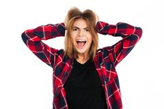 Screaming angry young woman standing isolated. Image of screaming angry young woman standing isolated over white wall background. Looking camera Royalty Free Stock Image
