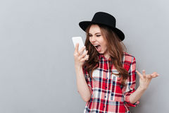 Screaming angry young woman talking by mobile phone. Image of screaming angry young woman standing over grey wall wearing hat talking by mobile phone. Looking Stock Photography