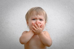 Screaming baby covering mouth by hand Stock Photos