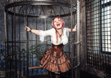 Screaming beautiful steampunk woman in the cage Stock Photos