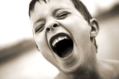Screaming boy. A black and white closeup of a boy's face as he screams out loud royalty free stock image