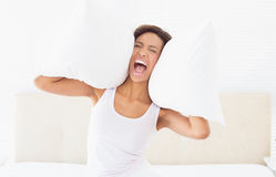 Screaming brunette sitting on bed covering ears with pillow Royalty Free Stock Photo