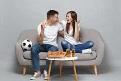 Screaming couple woman man football fans cheer up support favorite team looking at each other spreading hands isolated. Screaming couple women men football fans stock photo