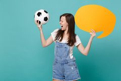 Screaming crazy girl football fan cheer up support team with soccer ball empty blank yellow Say cloud speech bubble. Isolated on blue turquoise background stock photography